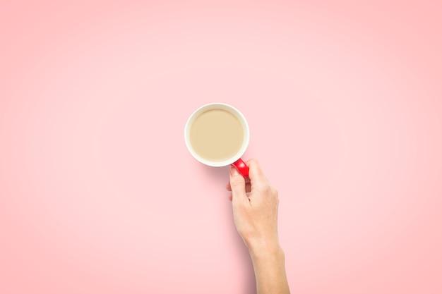 Een hand houdt een kopje met warme koffie op een roze achtergrond. ontbijtconcept met koffie of thee. goedemorgen, nacht, slapeloosheid. plat lag, bovenaanzicht