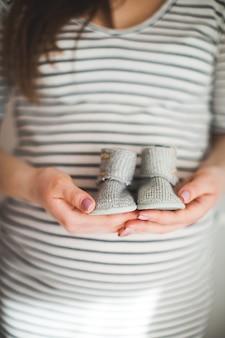 Een hand houdt een paar kleine schoenen vast. het zijn schoenen voor baby's. moeder en babythema. zwangere vrouw. geluk