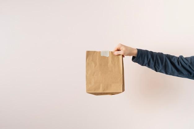 Een hand houdt een papieren pakketje vast met eten aan huis geleverd