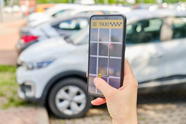 Een hand houdt een smartphone vast met een taxi-applicatie die de beweging naar de plaats laat zien