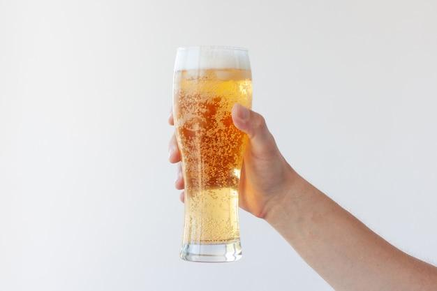 Een hand houdt een vol glas light bier met bubbels en schuim op een witte achtergrond.