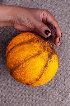 Een hand houdt een zelfgemaakte oranje pompoen van papier-maché voor halloween op een jute-oppervlak