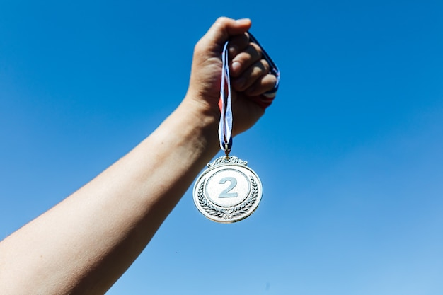 Een hand houdt een zilveren medaille op de tweede plaats omhoog, met de lucht op de achtergrond. overwinning concept