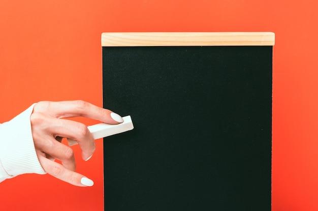 Een hand houdt een zwarte krijt-tablet op een rode achtergrond. meisje met witte manicure houdt wit krijt.
