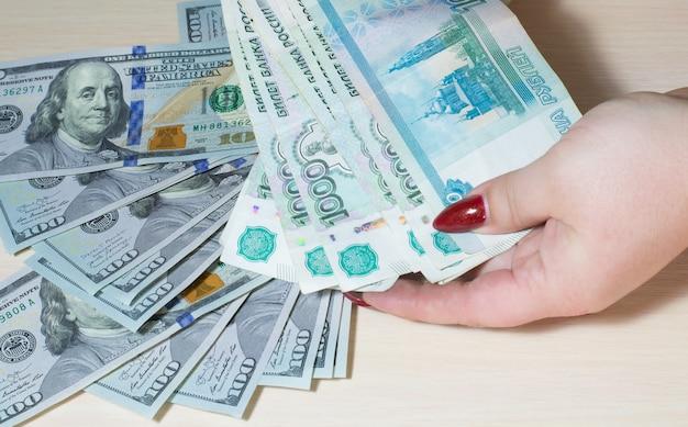 Een hand houdt russische roebels vast in coupures van 1000 tegen de achtergrond van 100 dollarbiljetten die in wanorde op tafel liggen.