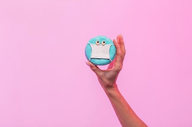 Een hand houdt zoete donut geïsoleerd op roze achtergrond