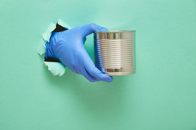 Een hand in een blauwe beschermende rubberen handschoen houdt een ijzeren blik met vleesstoofpot vast. ruimte groene achtergrond kopiëren