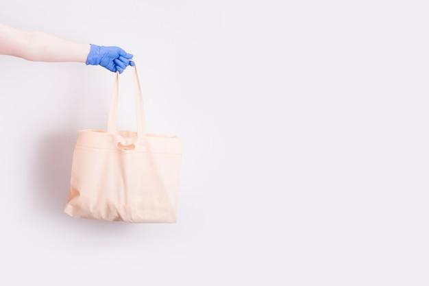 Een hand in een blauwe medische rubberen wegwerphandschoen houdt een boodschappentas vast om te winkelen