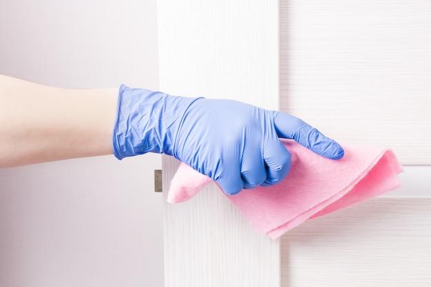 Een hand in een blauwe rubberen wegwerphandschoen veegt een deurknop af met een roze doek, reinigt en desinfecteert oppervlakken