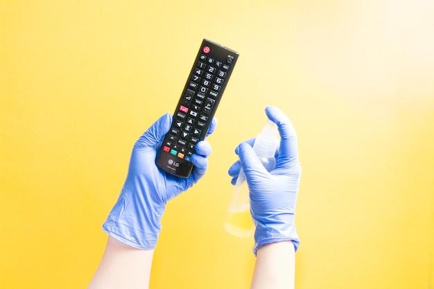 Een hand in een eenmalige rubberen handschoen is het besproeien van een tv-afstandsbediening van lg met een ontsmettingsmiddel op basis van alcohol