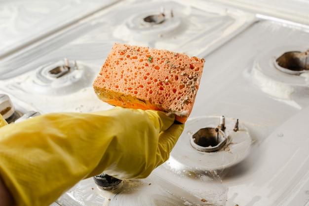 Een hand in een gele handschoen heeft een vuile spons.