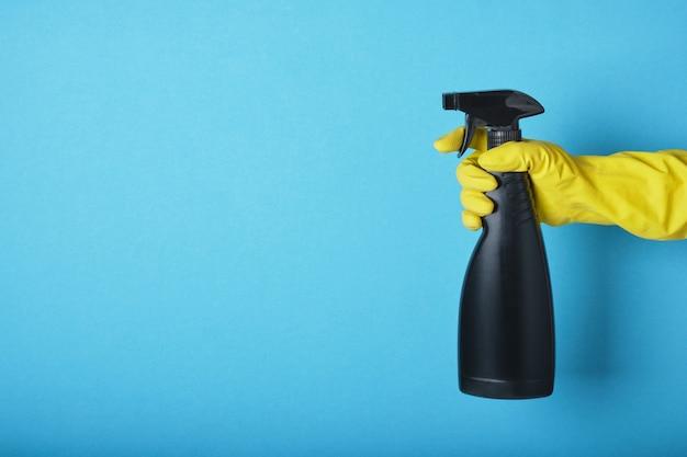 Een hand in een gele handschoen houdt een zwarte spuitfles reinigingsvloeistof op een blauwe achtergrond