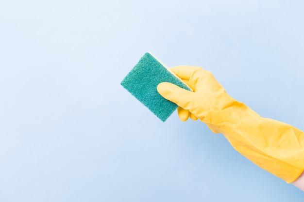 Een hand in een gele rubberen handschoen houdt een gele spons vast met een groene ruwe kant voor het reinigen van complex vuil