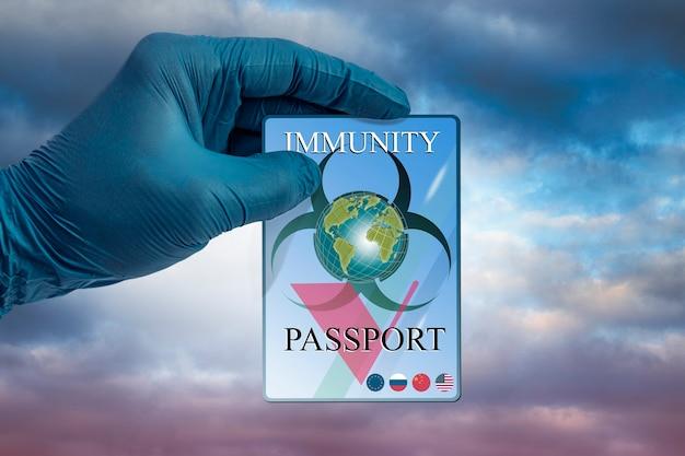 Een hand in een medische handschoen heeft een immuniteitspaspoort paspoort dat immuniteit tegen coronavirus bevestigt