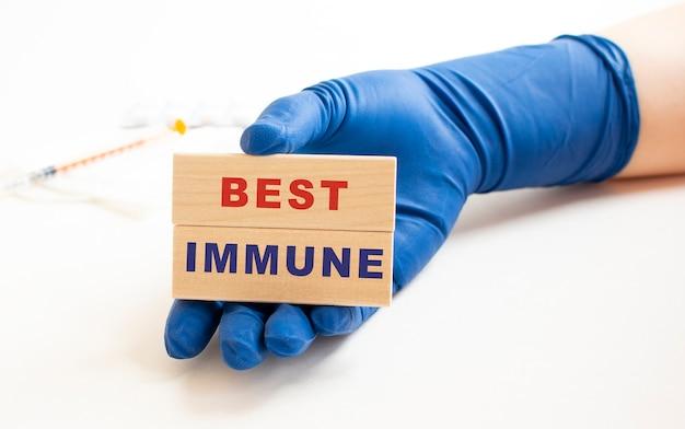 Een hand in een medische handschoen houdt houten kubussen vast met de inscriptie beste immuun. medisch concept.