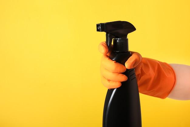 Een hand in een oranje handschoen houdt een zwarte spuitfles reinigingsvloeistof op een gele achtergrond