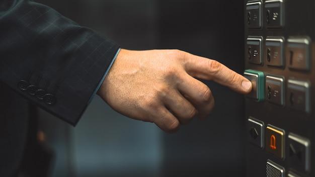 Een hand in een pak wordt uitgestrekt om op de vloerknop te drukken en de lift te starten.
