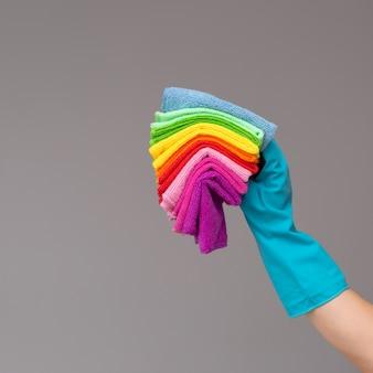 Een hand in een rubberen handschoen bevat een set gekleurde microfiberdoeken