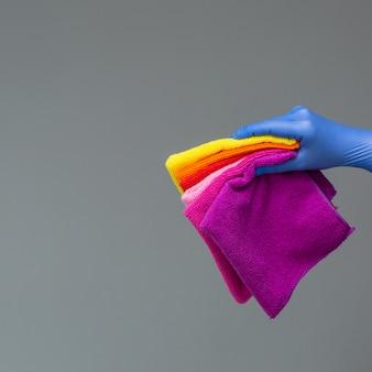 Een hand in een rubberen handschoen bevat een set gekleurde microvezeldoeken