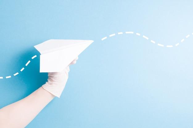 Een hand in een rubberen handschoen houdt een papieren vliegtuigje op een lichtblauwe achtergrond, kopie ruimte