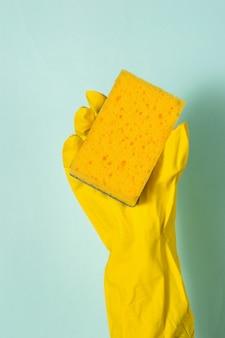 Een hand in een rubberen handschoen houdt een schuimspons op een blauw oppervlak