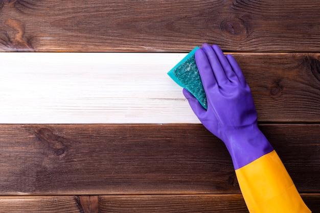 Een hand in een rubberen handschoen wast een houten oppervlak. schoonmaak, kamer schoonmaak.