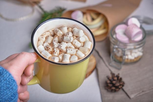 Een hand in een trui houdt een gele kop met cacao versierd met marshmallows vast, een standaard gemaakt van zaaggesneden hout en marshmallows op de achtergrond