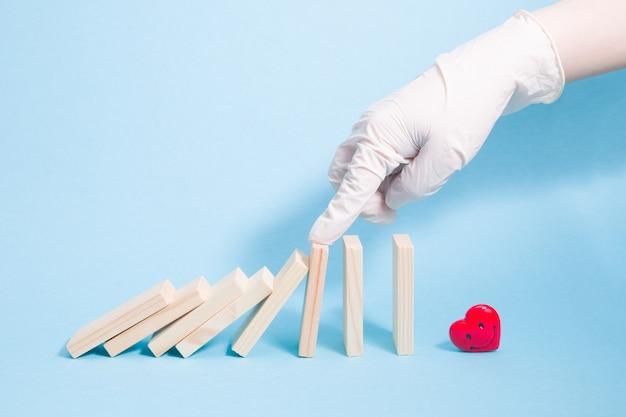 Een hand in een witte rubberen handschoen laat vallende dominostenen achter