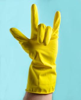 Een hand in gele rubberen handschoenen toont een steenhoorn, twee vingers omhoog