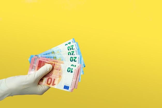 Een hand in medische handschoenen houdt eurobiljetten. quarantaine contant donatie concept