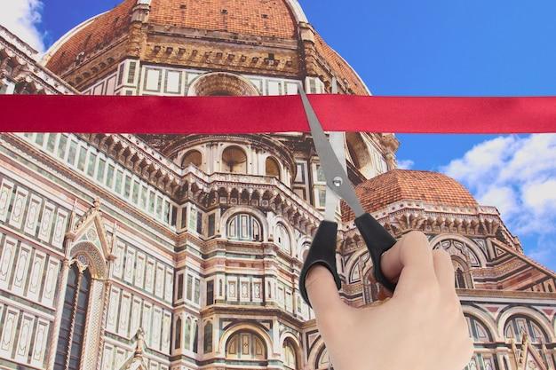 Een hand knipt een rood lint met een schaar en kijkt uit over de kathedraal