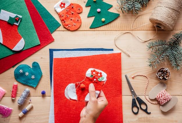 Een hand met doe-het-zelf vilten kerstsok, kerst- en nieuwjaarsknutsels voor kinderen