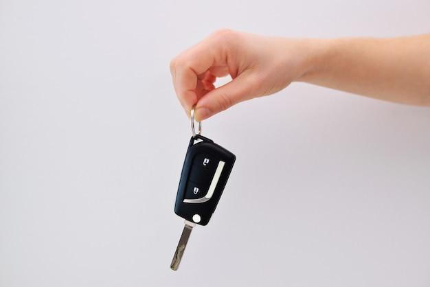 Een hand met een autosleutel op een witte achtergrond.