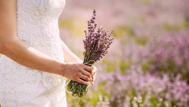 Een hand met een bloem op het veld