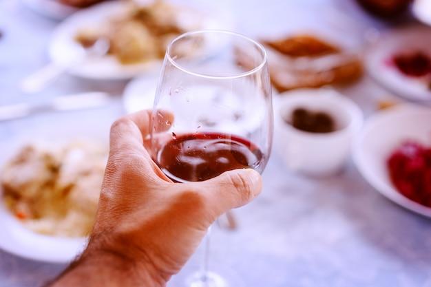 Een hand met een glas wijn