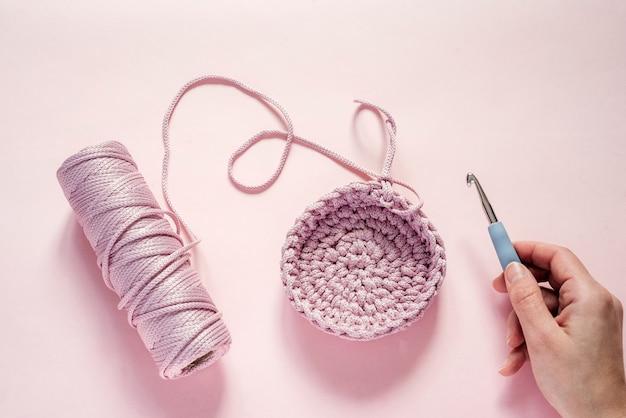 Een hand met een haaknaald en roze kleurgaren op een roze achtergrond, brei- en haakbenodigdheden, hobby en handwerk