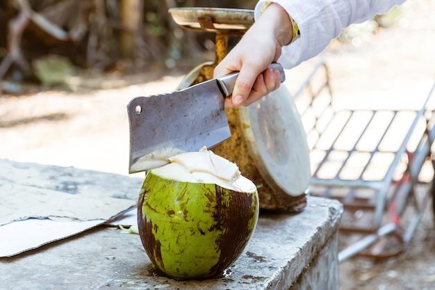 Een hand met een hakmes die verse groene kokosnoot snijdt.