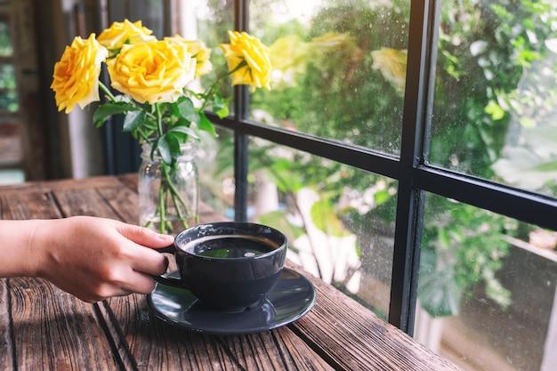 Een hand met een kop warme koffie op houten tafel
