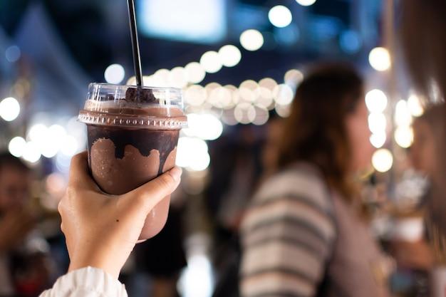 Een hand met een kopje cacao smoothie.