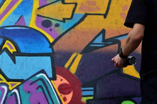 Een hand met een spuitbus die een nieuwe graffiti op de muur tekent