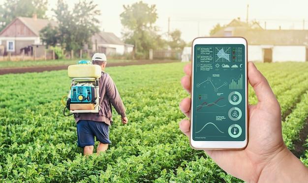 Een hand met een telefoon op de achtergrond van een boer met landbouwrookmistspuitmachine