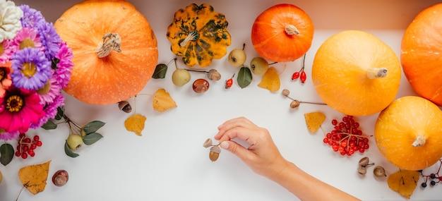 Een hand met eikel over pompoenen en gedroogde bladeren herfstlay-out