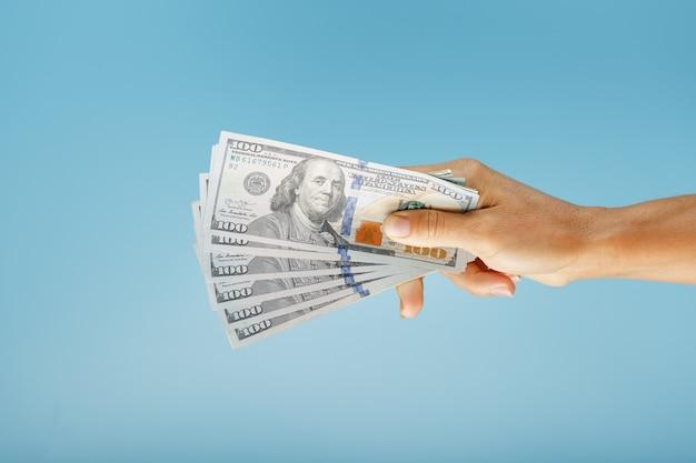 Een hand met honderd dollarbiljetten op een blauw.