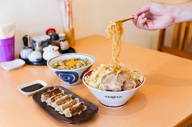 Een hand met noodle door stokjes van tonkotsu chashu ramen met butadon en gyoza.