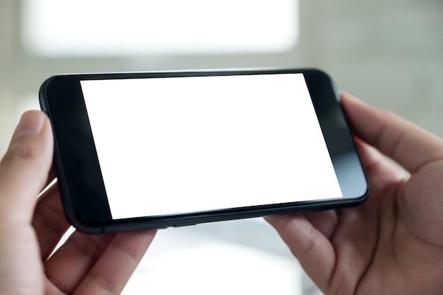 Een hand met zwarte mobiele telefoon met lege witte bureaubladscherm