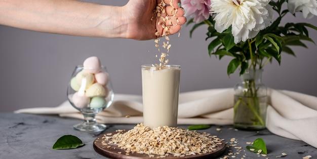 Een hand morst havervlokken in een glas natuurlijke havermelk op tafel