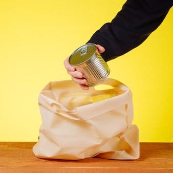 Een hand neemt het blikje uit de papieren boodschappentas
