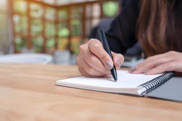 Een hand opschrijven op een witte lege notebook op houten tafel