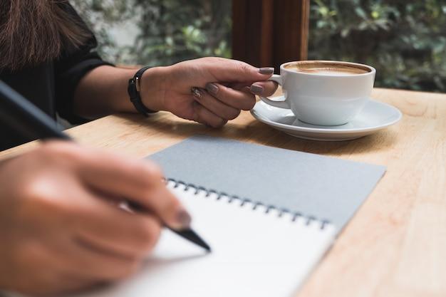 Een hand opschrijven op een witte lege notebook terwijl het drinken van koffie op houten tafel