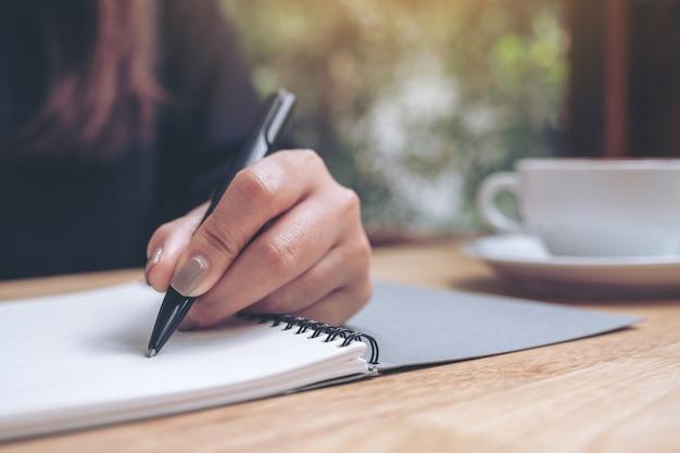 Een hand schrijft op een notitieboekje met koffiekop op houten lijst neer
